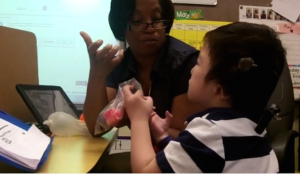 Student communicates with an intervener by signing 'want'